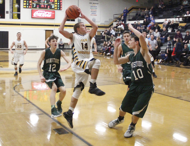 Iron Mountain freshman point guard Marcus Johnson drives to the basket against Manistique on Thursday. Johnson scored 24 points in the Mountaineers' 76-26 win. (Adam Niemi/The Daily News)