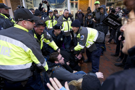 Police try to remove demonstrators from attempting to block people entering a security checkpoint, Friday, Jan. 20, 2017, ahead of President-elect Donald Trump's inauguration in Washington. (AP Photo)