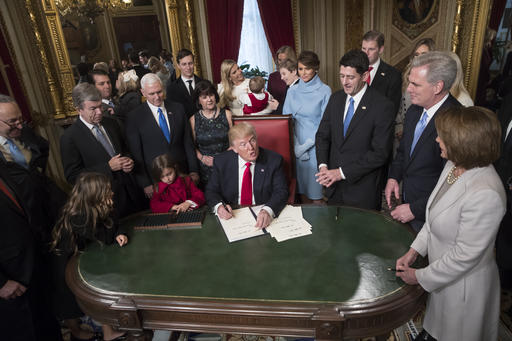 President Donald Trump is joined by the Congressional leadership and his family as he formally signs his cabinet nominations into law, in the President's Room of the Senate, at the Capitol in Washington, Friday, Jan. 20, 2017. From left are Senate Minority Leader Chuck Schumer, D-N.Y., Sen. Roy Blunt, R-Mo., Donald Trump Jr., Vice President Mike Pence, Jared Kushner, Karen Pence, Ivanka Trump, Barron Trump, Melania Trump, Speaker of the House Paul Ryan, R-Wis., Majority Leader Kevin McCarthy, D-Calif., House Minority Leader Nancy Pelosi, D-Calif. (AP Photo)