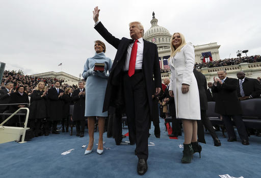 President Donald Trump waves after taking the oath of office as his wife Melania holds the Bible, and Tiffany Trump looks out to the crowd, Friday, Jan. 27, 2017 on Capitol Hill in Washington. (AP Photo)