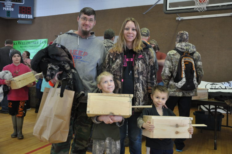 Hunter and Eli Kordish of Wallace show off their free weasel boxes at last year's trappers workshop in Hermansville. From left, are Andrew, Hunter, Kerry and Eli.
