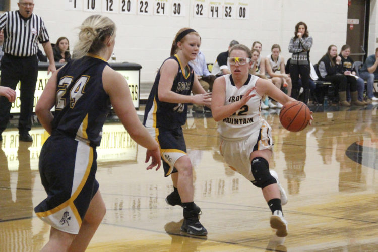 Iron Mountain's Riley Poupore, right, drives to the basket against Bark River-Harris on Friday in Iron Mountain. (Adam Niemi/The Daily News)