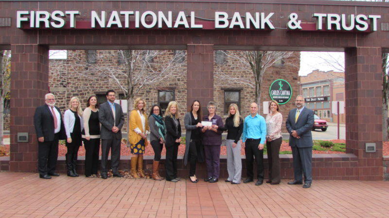 IRON MOUNTAIN ROAD & Trail Half Marathon Committee members presented the 2016 donation of $16,000 to the Dickinson County Cancer Loan Closet at First National Bank & Trust. Shown here, from left, are Steve Faust; Ashley Smith; Nicole Lutz; Matt Lutz, committee treasurer; Sharon Socia; Audrey Hutchinson; Sandy Petroff; Lisa Villringer, committee president and race director; Diane Schabo, president of the Loan Closet; Melissa Wentarmini, committee Secretary and co-director of the race;  Steve Lehmann, committee vice president; Sue Glime; and Dave Kashian.