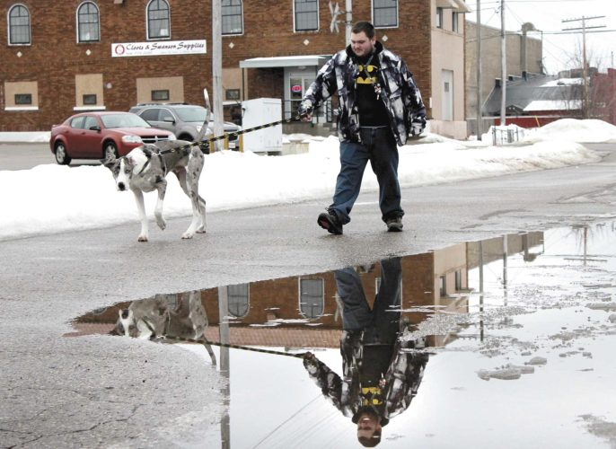 CODY COLE OF Iron Mountain and dog Tyson navigate through the puddles and slush on Merritt Avenue in Iron Mountain. (Theresa Proudfit/Daily News photo)