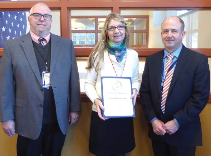 AFTER 25 YEARS of service, Deborah Skoglund-White, center, receives her retirement certificate from Jim Rice, right, director of the Oscar G. Johnson VA Medical Center; along with Paul Seim, left, assistant chief of nursing and patient care service.