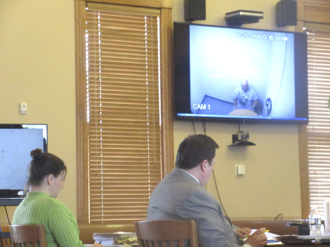 KELLY COCHRAN, LEFT, and defense attorney Michael Scholke are pictured in Iron County Trial Court as a police interview video of Cochran's now-deceased husband, Jason Cochran, plays in the upper right corner. Cochran is accused of helping her husband kill 53-year-old Christopher Regan of Iron River and hiding the remains in October 2014. (Nikki Younk/Daily News photo)