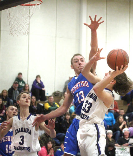Peshtigo's Riley Demmith (13) goes up to block a shot by Niagara's Kalvin Jeffords (33) on Thursday during a M&O Conference game. (Theresa Proudfit/The Daily News)