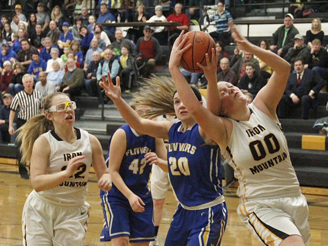 Kingsford's Hannah Cross (20) battles for a rebound against Iron Mountain's Emma Thomann (00) as Riley Poupore (32) follows the play on Friday in Iron Mountain. (Adam Niemi/The Daily News)
