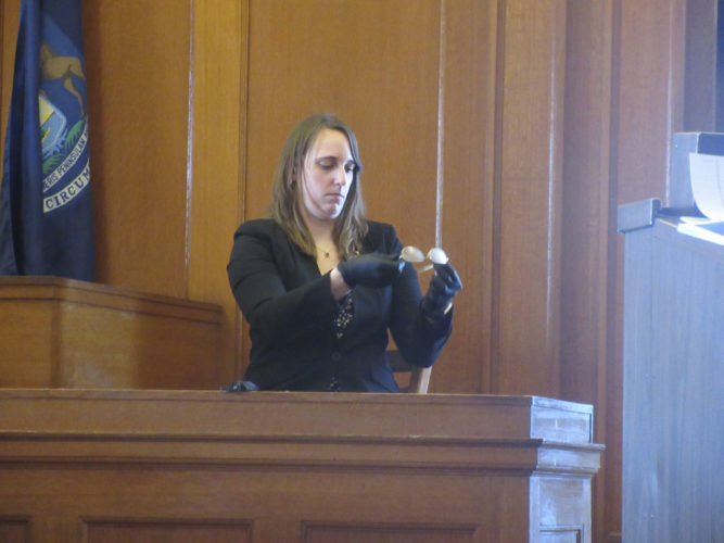 Nikki Younk/Daily News Photos  Forensic scientist Lisa Oravetz holds up what are believed to be murder victim Christopher Regan's eyeglasses in Iron County Trial Court. The glasses and Regan's skull were located in May 2016, about a year and a half after Kelly Cochran and her husband reportedly killed Regan.