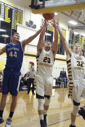 Iron Mountain's Josh Tucker (20) and Charlie Gerhard (32) battle Ishpeming's Hart Holmgren (44) for a rebound Monday in Iron Mountain. (Adam Niemi/The Daily News)