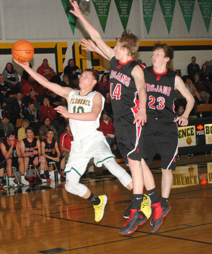 Florence's Jay Walstrom (10) attempts to put up a shot past Forest Park's Josh Logan (14) and Dodge Isaacson (23) in Monday's game. (Burt Angeli/The Daily News)