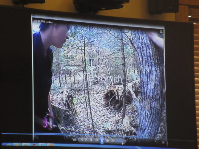 KELLY COCHRAN IS shown on police body camera footage guiding investigators to the area off of Pentoga Trail where she and her now-deceased husband, Jason Cochran, dumped the remains of 53-year-old Christopher Regan. Regan's glasses were found near the downed tree, and his skull was later discovered in a clearing not far from the area. (Nikki Younk/Daily News photo)