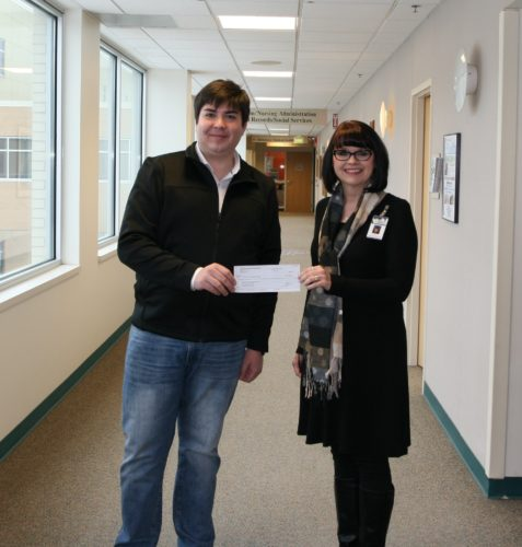 RECEIVING A $500 sponsorship check from Dan Freeman, public relations for Spine Pain Diagnostics, is Teresa Schettler, public relations-marketing specialist with Dickinson County Healthcare System and WOW Conference event chair. The conference is scheduled for March 4 at Pine Grove Country Club in Iron Mountain.