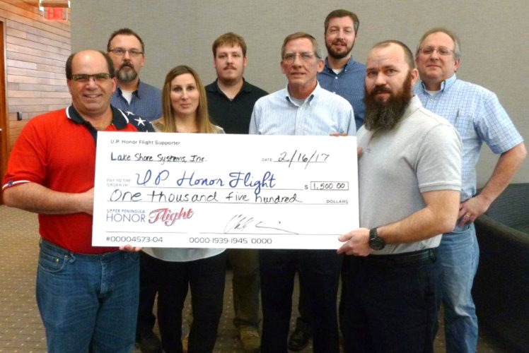 A DONATION OF $1,500 was presented by Lake Shore Systems Inc. employees in Kingsford to the Upper Peninsula Honor Flight, which supports missions that transports veterans to Washington, D.C. to visit monuments and memorials. Shown here in front, from left, are Scott Knauf of the U.P. Honor Flight with Lake Shore employees Jamie Phillips, Steve Thiry and Chuck Cain. In back, from left, are employees Aaron Kadish, John Schuman, Fritz Wenzel and John Biesterveld.
