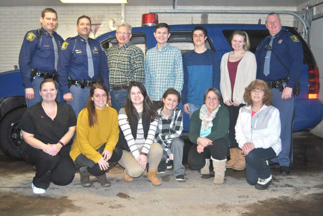 KINGSFORD HIGH SCHOOL students participated in a mock exercise using Critical Incident Stress Management (CISM) with the Michigan State Police Post in Iron Mountain. Shown here in front from left are Jeananne Sheltrow, Elyse Damico, Alissa Kainrath, Nicci Hofer, Anita Leeman, and Lisa Woods. In back from left are Trooper Steve Boyer, Trooper Geno Basanese, Joe Hruska, Mitchell Wiltzius, Dominic Occhietti, Chloe Gabbert and Trooper Scott Ritsema.