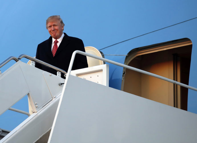 President Donald Trump disembarks Air Force One as he returns Sunday at Andrews Air Force Base, Md. after a weekend at Mar-a-Largo, Fla. (AP Photo/Alex Brandon)