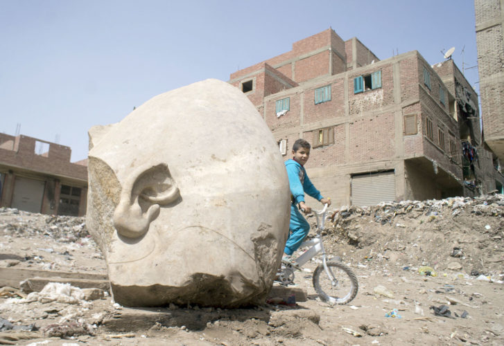 A boy rides his his bicycle past a recently discovered statue in a Cairo slum that may be of pharaoh Ramses II, in Cairo, Egypt, Friday. Archeologists in Egypt have discovered a massive statue that may be of pharaoh Ramses II, one of the country's most famous ancient rulers. The colossus, whose head was pulled from mud and groundwater by a bulldozer on Thursday, is around eight meters (yards) tall and was discovered by a German-Egyptian team.