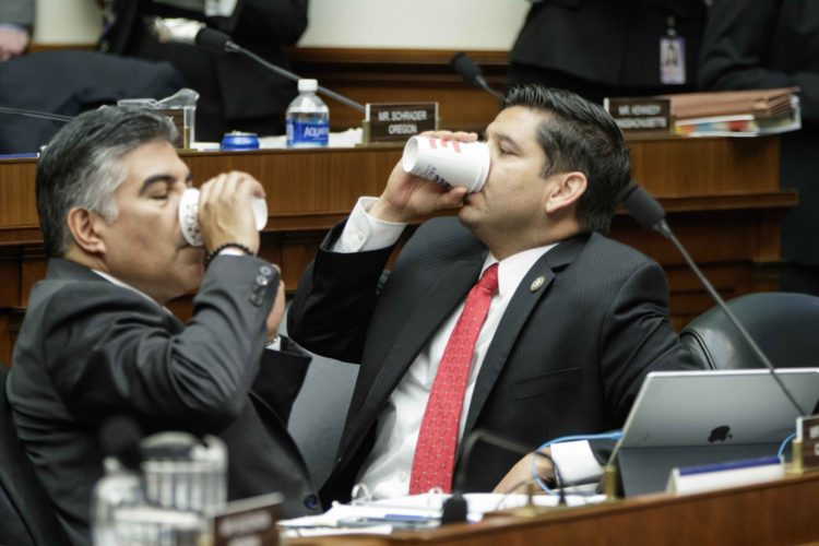 """HOUSE ENERGY AND Commerce Committee member Rep. Tony Cardenas, D-Calif., left, and Rep. Raul Ruiz, D-Calif., refuel as members of the committee argue the details of the GOP's """"Obamacare"""" replacement bill after working all night, Thursday on Capitol Hill. AP Photo/J. Scott Applewhite"""