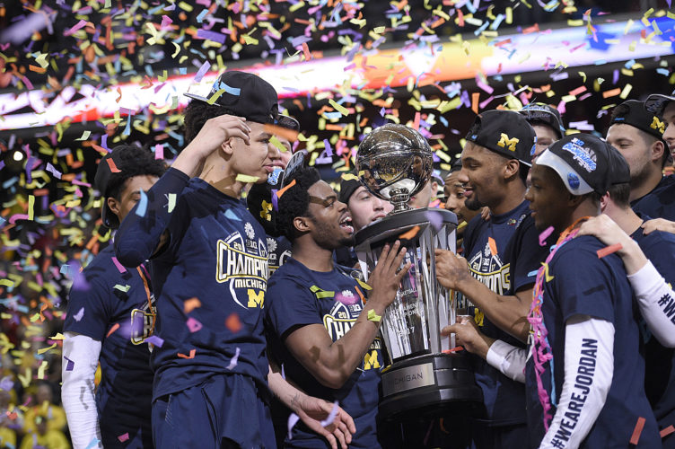 Michigan celebrates with the trophy after the Big Ten championship game against Wisconsin on Sunday in Washington. Michigan won 71-56. (AP Photo/Nick Wass)