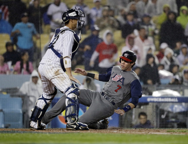 United States' Christian Yelich scores past Japan catcher Seiji Kobayashi during the fourth inning of a semifinal in the World Baseball Classic in Los Angeles on Tuesday. (AP Photo/Chris Carlson)
