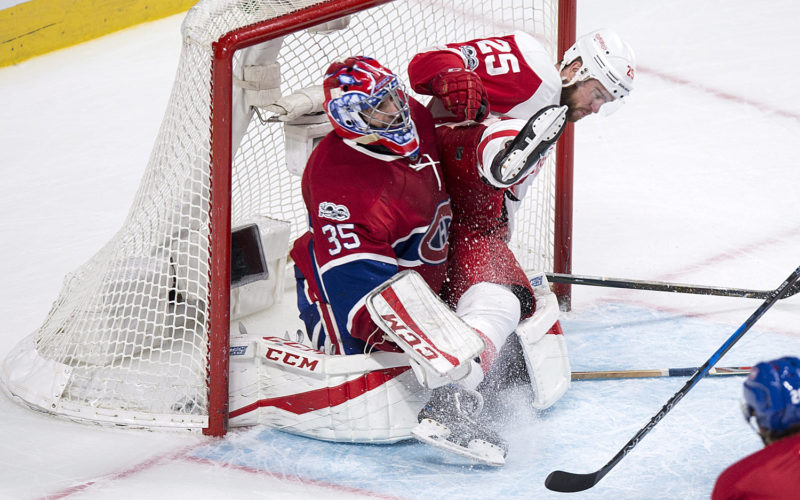 Detroit Red Wings' Mike Green (25) flies into Montreal Canadiens goalie Al Montoya (35) during overtime in Montreal on Tuesday. (Paul Chiasson/The Canadian Press via AP)