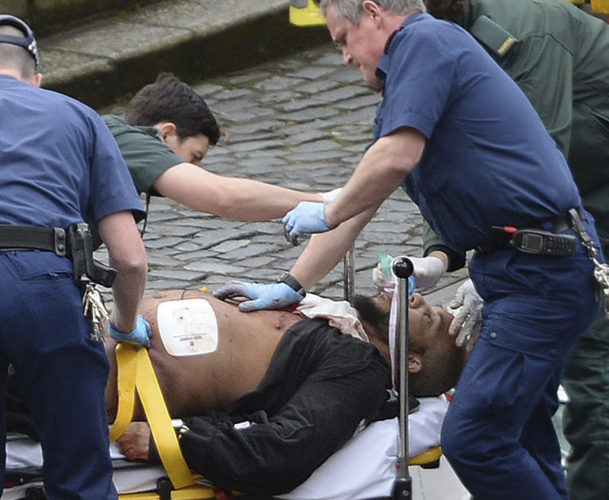 "Someone identified by the Associated Press as an attacker in the terror incident in London is treated by emergency services outside the Houses of Parliament. London police say they are treating the attacks ""as a terrorist incident until we know otherwise."" Officials say a man with a knife attacked a police officer at Parliament and was shot by officers. Nearby, witnesses say a vehicle struck several people on the Westminster Bridge. (Stefan Rousseau/PA via AP)."