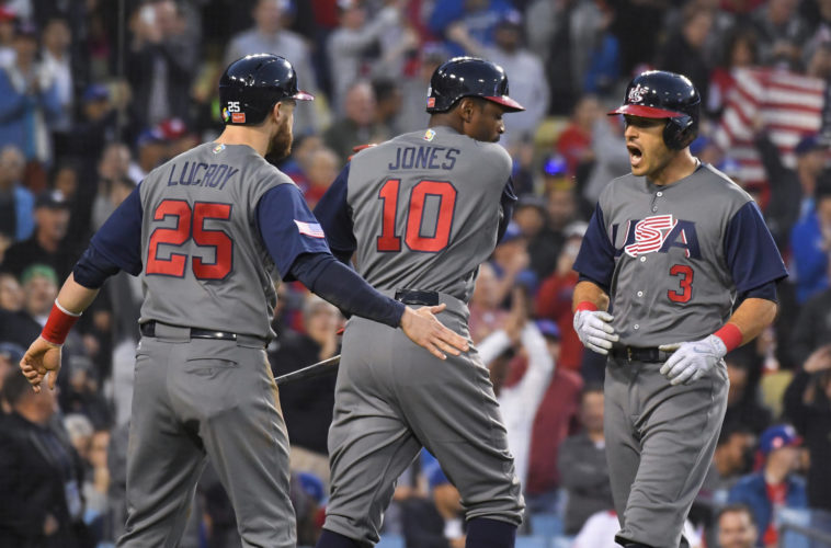 United States' Ian Kinsler, right, celebrates his two-run home run with Jonathan Lucroy, left, and Adam Jones during the third inning against Puerto Rico in the final of the World Baseball Classic in Los Angeles on Wednesday. (AP Photo/Mark J. Terrill)