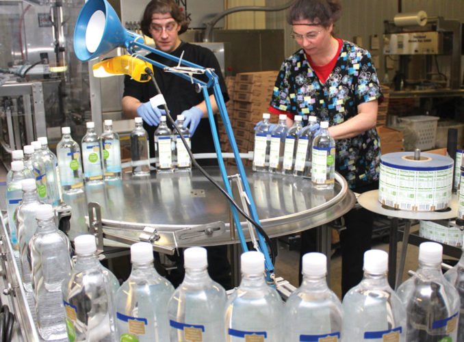 DYLAN ROSE AND Susan Polaske inspect each bottle of water as it comes down the assembly line at Crystal Falls Springs Inc. in Crystal Falls. (Theresa Proudfit/Daily News photo)