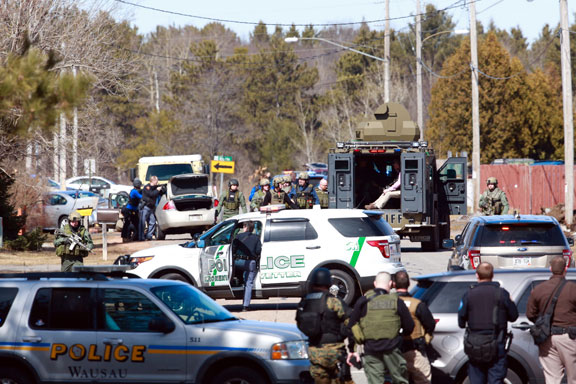 Numerous law enforcement vehicles and SWAT teams respond to a shooter Wednesday at an apartment complex in Rothschild, Wis. Four people including a police officer are dead and a suspect is in custody. The shootings happened at a bank, a law firm and an apartment complex, where officers, including a SWAT team, were in a standoff with the suspect late in the afternoon, Wausau police Capt. Todd Baeten said at a news conference. The area is about 90 miles west of Green Bay. (AP photo)