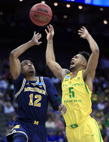 Michigan guard Muhammad-Ali Abdur-Rahkman (12) shoots over Oregon guard Tyler Dorsey (5) during the first half of a regional semifinal of the NCAA tournament on Thursday in Kansas City, Mo. (AP Photo/Orlin Wagner)