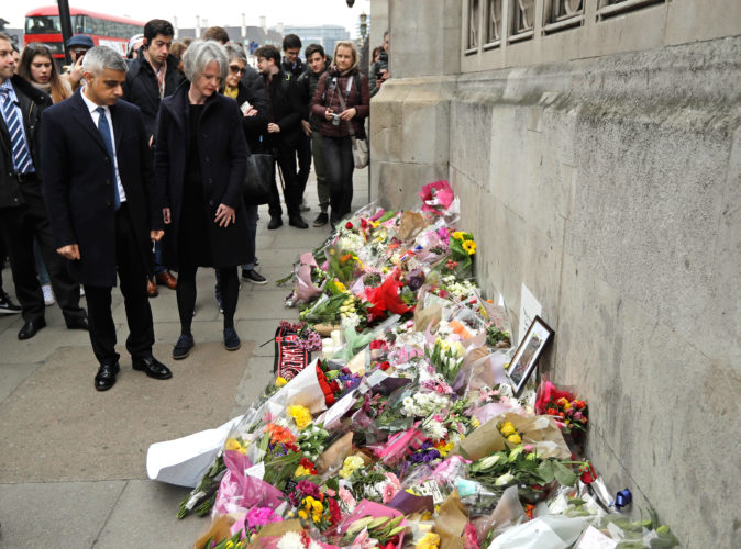 AP Photo  London Mayor Sadiq Khan looks at floral tributes to victims of Wednesday's attack outside the Houses of Parliament in London, Friday. On Thursday authorities identified a 52-year-old Briton as the man who mowed down pedestrians and stabbed a policeman to death outside Parliament in London, saying he had a long criminal record and once was investigated for extremism — but was not currently on a terrorism watch list.
