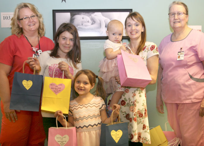 """Kristin and Eric Glaser wanted to do something nice with a portion of their income tax refund. The couple asked their daughters, """"What should we do?"""" and they unanimously voted to use the money to create gift bags for newborn babies. The gift bags are gender specific and contain a new baby bear and a baby's first soft sided picture book. Thirty gift bags were prepared and donated to the Dickinson County Hospital System's Family Birth Center. The bags will be given to the first 30 newest members of the community. """"The girls were so excited to donate the bags and luckily they were able to hand the very first bag out in person,"""" says a hospital spokesperson. """"It is a very kind gesture by the Glaser family and our hospital is proud to hand them out on their behalf."""" Pictured from left are Dee McDonald, RN; Kristina Gauger; Evelyn Glaser; Elizabeth Glazer; Kristin Glaser; and Cindy Gordon, RN."""