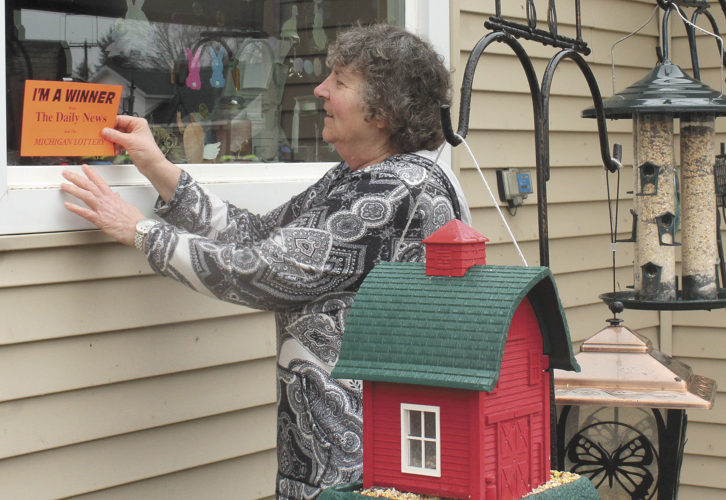 """Cindy Steele places The Daily News """"I'm a Winner"""" sign in the window of her home on Newton Street in Kingsford. Over the years, The Daily News has given away more than 30,000 instant lottery tickets through this promotion. Theresa Proudfit/Daily News Photo"""