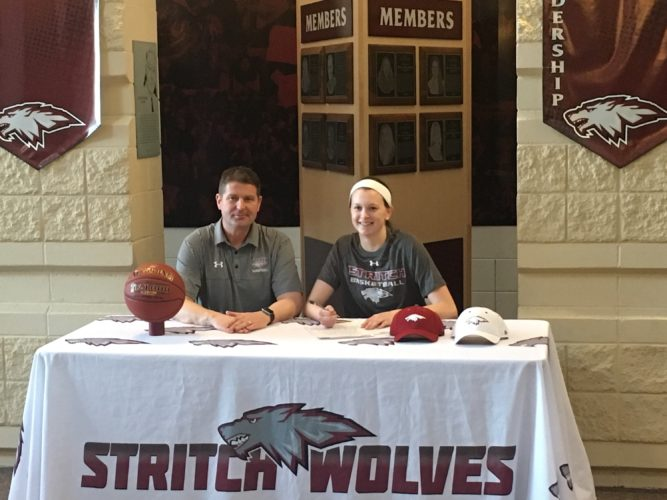 Courtesy Photo/Cardinal Stritch University  Kingsford's Maria Wiltzius signs a college basketball letter of intent to Cardinal Stritch University in Milwaukee as Wolves head coach John Pfaffl looks on.