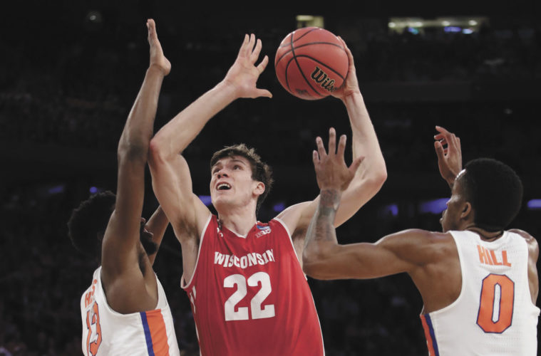 Wisconsin's Ethan Happ (22) drives to the basket against Florida's Kevarrius Hayes (13) and Kasey Hill (0) in the first half of Friday's NCAA East Regional semifinal in New York.  AP Photo