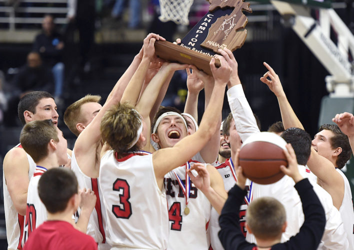 North Central's Seth Polfus, center, and teammates celebrate with the Class D state championship trophy after beating Buckley 78-69 on Saturday at the Breslin Center in East Lansing. The title was North Central's third-straight championship. (J. Scott Park/Jackson Citizen Patriot via AP)