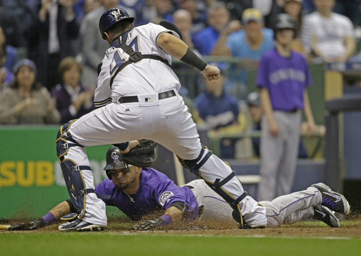 Colorado Rockies' Gerardo Parra is tagged out at home plate by Milwaukee Brewers catcher Jett Bandy during the seventh inning of an opening day baseball game Monday, April 3, 2017, in Milwaukee. (AP Photo/Jeffrey Phelps)