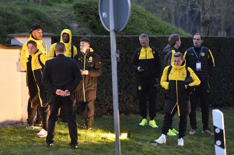 Head coach Thomas Tuchel, right, and players of Borussia Dortmund stand outside their team bus after it was damaged in an explosion before the Champions League quarterfinal soccer match between Borussia Dortmund and AS Monaco in Dortmund, western Germany on Tuesday.  (AP Photo/Martin Meissner)