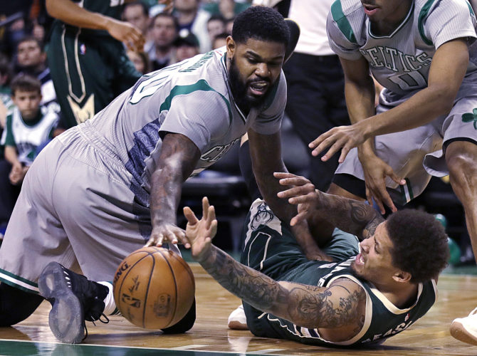 Milwaukee Bucks forward Michael Beasley, right, battles for a loose ball with Boston Celtics forward Amir Johnson (90) during the second half in Boston on Wednesday. (AP Photo/Charles Krupa)
