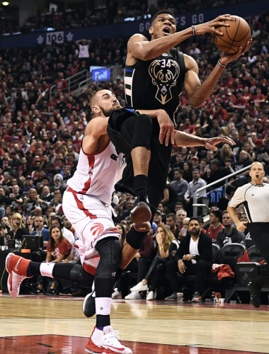 Milwaukee Bucks forward Giannis Antetokounmpo (34) drives past Toronto Raptors center Jonas Valanciunas (17) during a first-round NBA playoff game in Toronto on Saturday. (Frank Gunn/The Canadian Press via AP)
