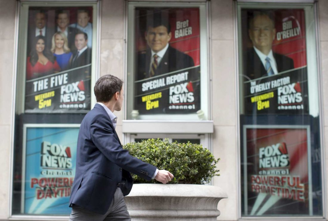 """AP Photo/Mary Altaffer  A pedestrian walks past the News Corp. headquarters building in New York displaying posters featuring Fox News Channel personalities including Bill O'Reilly, right, on Wednesday. O'Reilly has lost his job at Fox News Channel following reports that five women had been paid millions of dollars to keep quiet about harassment allegations. 21st Century Fox issued a statement Wednesday that """"after a thorough and careful review of the allegations, the company and Bill O'Reilly have agreed that Bill O'Reilly will not be returning to the Fox News Channel."""