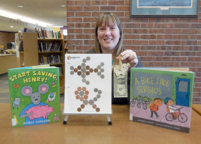 """Children's Specialist Emily Cummings, posing with the books and crafts for """"Money Smart: How to Make Cents."""""""