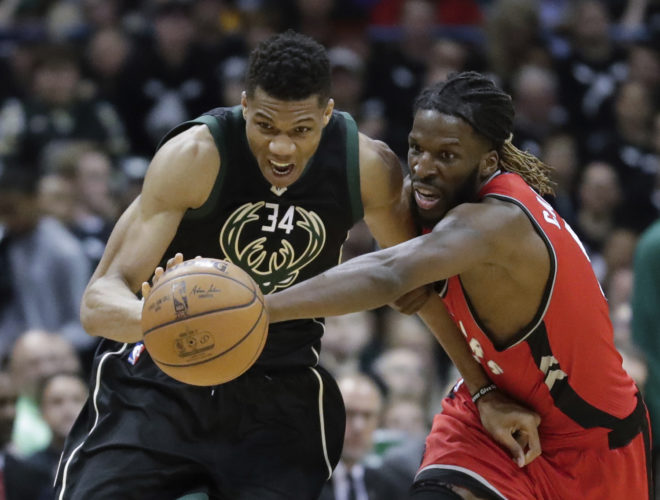 Toronto's DeMarre Carroll and Milwaukee Bucks' Giannis Antetokounmpo go after a loose ball during the second half of game 3 of their NBA first-round playoff series basketball game Thursday in Milwaukee. The Bucks won 106-77. (AP Photo/Morry Gash)