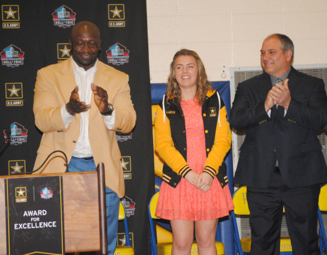 Burt Angeli/The Daily News Photo Kingsford High School senior Katelyn Hicks received the Award for Excellence jacket and finalist plaque from the US Army and Pro Football Hall of Fame during a ceremony Friday in the middle school gym. John Randle, a Pro Football Hall of Famer, presented the awards. Kingsford teacher and softball coach Kevin Murdock (right) nominated Hicks.