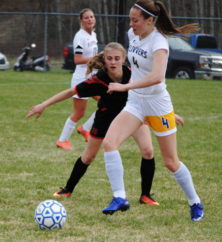 Kingsford's Peyton Johnson (4) and Marquette's Reegan Ketzenberger (16) rush for the ball Tuesday at Commemorative Field. (Burt Angeli/The Daily News)