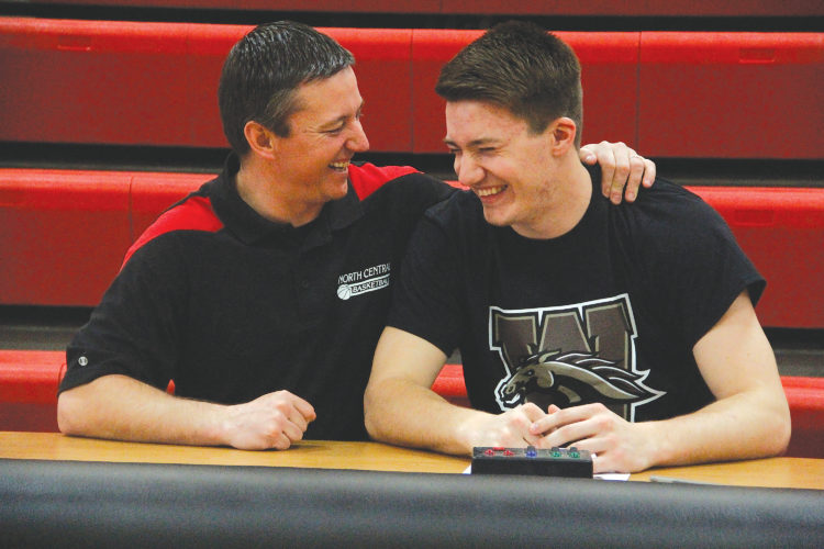 North Central senior Jason Whitens, right, shares a laugh with Jets' boys basketball coach Adam Mercier, left, on Friday in Powers. Whitens signed his letter of intent to play basketball at NCAA Division I Western Michigan University. (Adam Niemi/Iron Mountain Daily News)