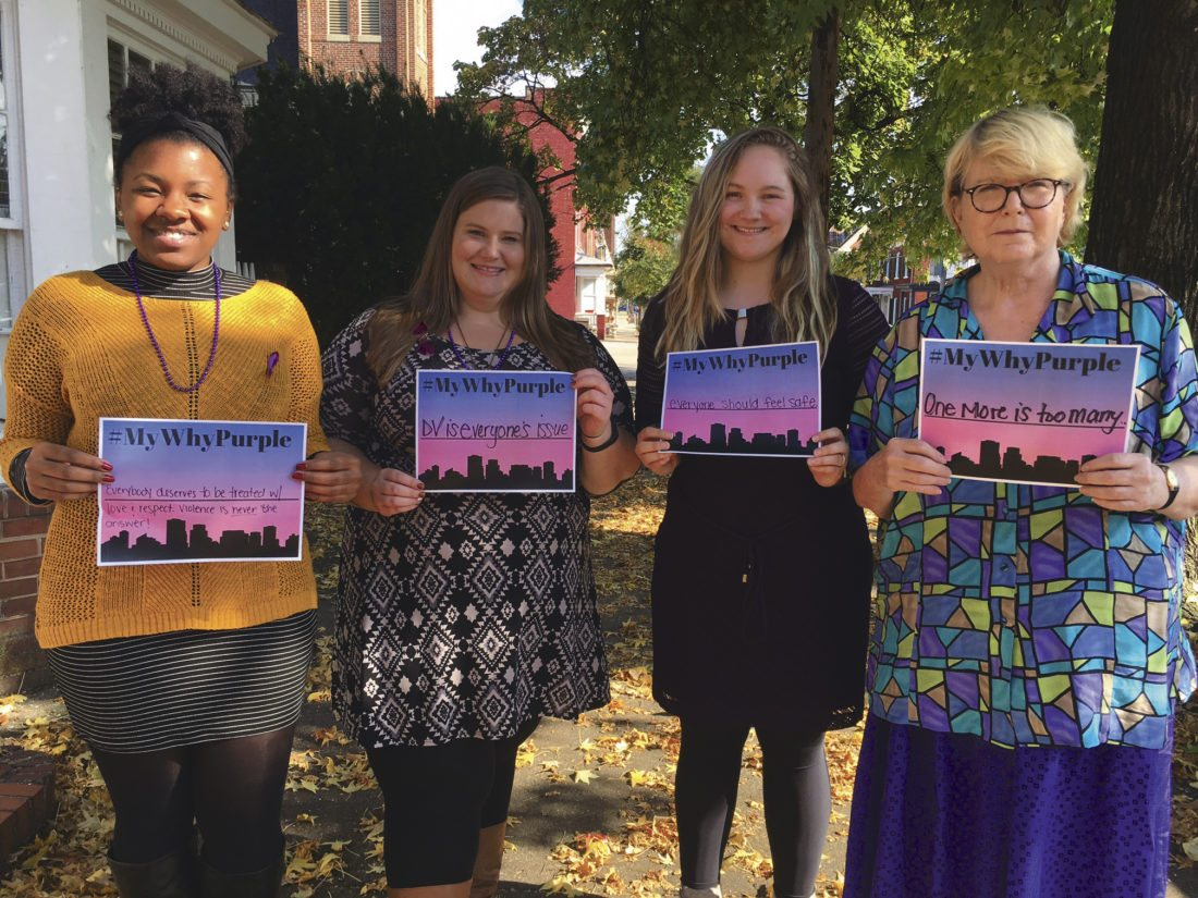 "Journal photo by Katiann Marshall From left, Vivian Baylor, sexual assault victim advocate; Katie Spriggs, program manager for Shenandoah Womens Center; Hannah Shockey, Shepherd University intern; and Rebecca Ramsey, volunteer, stand outside the center Thursday afternoon. The group is shown holding #mywhypurple signs to promote why they are wearing purple in honor of National Domestic Violence Awareness Month. See ""Community comes together to discuss domestic violence awareness"" on page B1."
