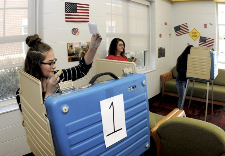 Journal photos by Ron Agnir 8th grader Abigail Wilson raises her hand after filling out her ballot to vote after the Channel One Election Day Assembly at Mountain Ridge Middle school Thursday morning.