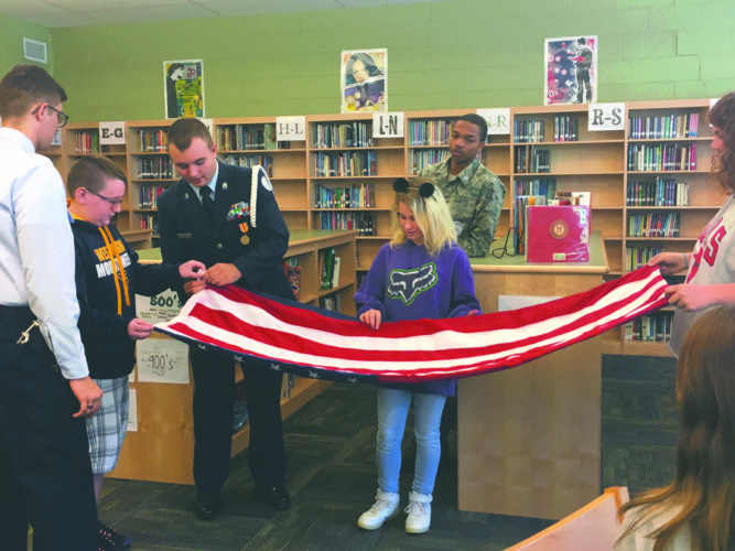 Journal photo by Katiann Marshall Students from North Middle School's flag patrol learn how to properly fold the American flag by cadets from Martinsburg High School's ROTC program.