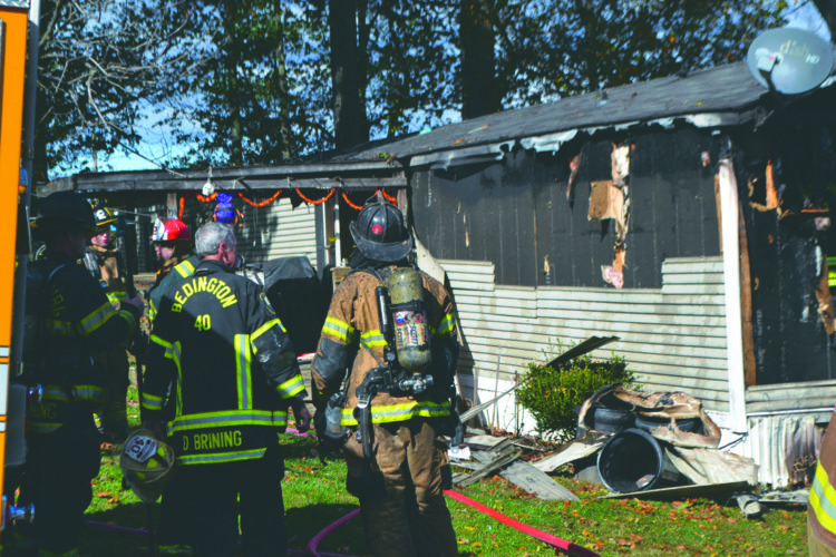 Journal photo by Mary Stortstrom Firefighters stand outside a mobile home in the Rock Glen Mobile Home Park in Hedgesville on Saturday.